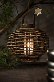 White pillar candle in wooden candle lantern hung from pine branch
