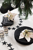 Table set in black and white and decorated with flowers for Christmas meal