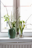 Vases of white spring flowers: tulip, anemone, willow catkins, waxflower, hyacinths, star-of-Bethlehem and cherry branch