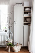 Cherry branches in glass demijohn on wooden stool
