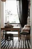 Wooden table and various seats in front of window