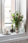 Frühlingsstrauß mit Tulpen und weiße Kerzen auf Fensterbank