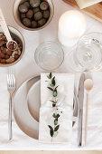 Gedeck mit Zweig dekoriert auf weißem Tischtuch