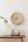 Ballonflasche, Glasgefäß und Keramikvase mit Gräsern auf Holzbank