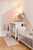 Cot and changing unit in pink and white nursery