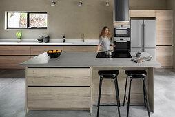 Barhocker an der Kücheninsel mit Kochfeld, Frau im Hintergrund