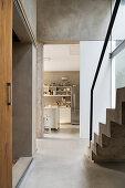 Blick vom Flur mit Betonboden und Treppe in die Küche