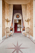 Pair of Louis-XVI-style dining chairs and gilt wall sconces in hallway with star inlaid in marble flooring