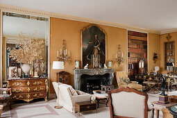 Large Georgian portrait above marble fireplace in drawing room with wall sconces and French chest of drawers