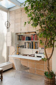 Fold-out desk with shelving in conservatory with terracotta wall tiles