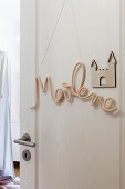 Crocheted name on door of child's bedroom
