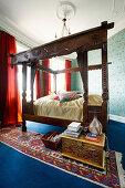 Antique, carved wooden bed in bedroom