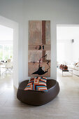 Designer pouffe with patterned scatter cushion below modern artwork on wall