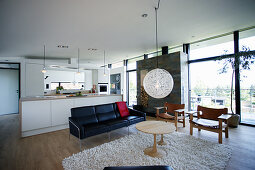 Kitchen and seating area in open-plan interior with glass wall
