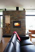 Black leather couch in front of fireplace