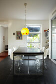 Dining table and classic chairs below pendant lamp with yellow lampshade