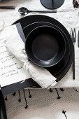 Black place setting with handwritten menu card