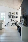 TV cabinet and bicycle in living room with white board floor and black accent wall