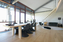 Long dining table and black, classic chairs in loft apartment