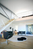 Open-plan interior with stairs leading to gallery in loft apartment