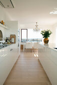 White, open-plan kitchen with island counter