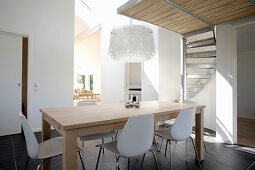 Dining table with classic chairs and spiral staircase in background