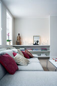 Pale sofa with scatter cushions in front of candles and head of Shiva on shelves