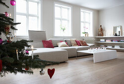 Christmas tree, pale sofa with scatter cushions and coffee table in living room