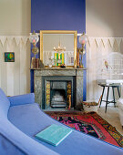 Blue couch in front of fireplace with blue chimney breast in living room