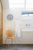 Chair below wall clock in white bathroom with skylight