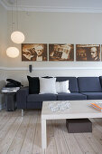 Row of photographs on wall above dark grey sofa, pendant lamps and coffee table on pale board floor in living room