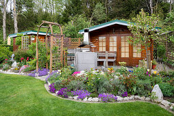 British garden with garden and tool shed, shrub bed, and rose arch