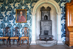 An antique cast iron stove, a portrait painting and chairs against a wall with blue patterned paper