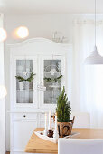A dining table with Christmas decorations in front of a white sideboard