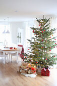 A Christmas tree with presents under it in front of a dining table