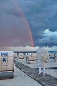 Mädchen mit Regenschirm am Strand mit Strandkörben, Regenbogen im Hintergrund