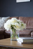 White peonies in a glass vase on a coffee table in front of a brown leather couch