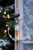 Weihnachtlicher Metallkranz mit Teelicht am Fenster