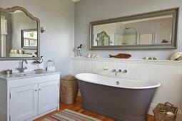 Free-standing bathtub, vanity and mirror in the bathroom