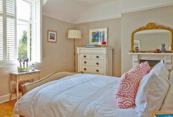 Double bed, white dresser and fireplace with mirror in the bedroom