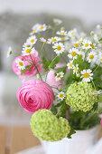 A bouquet of ranunculus, viburnum and feverfew