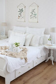 White bed with collection of scatter cushions, tray and bouquet of tulips