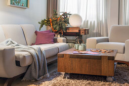 Pale upholstered sofa and coffee table wit h castors on a deep-pile rug in the living room