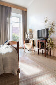TV next to potted palm, armchair with fur blanket and bookshelf in the bedroom
