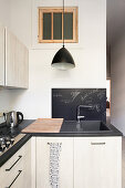 L-shaped fitted kitchen with light fronts and black worktop