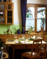 A wooden table laid with napkins and candles in a rustic country house kitchen