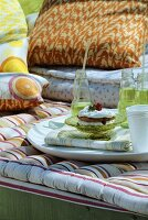 Small berry cake and water bottles on a sofa seat