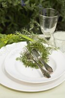 Place-setting with rosemary on table in garden