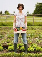 Woman holding crate of freshly picked vegetables in garden