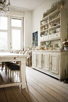 Kitchen with antique, white-painted wooden dresser and elegant, upholstered chairs at simple wooden table